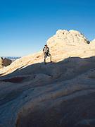 A hiker enjoys the beautiful scenery at White Pocket, Paria Plateau, Vermilion Cliffs National Monument, Arizona.