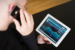Man checking performance of FTSE stock market data on iPad3 tablet computer