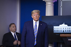 United States President Donald J. Trump listens as United States Vice President Mike Pence delivers remarks on the Coronavirus pandemic during a news conference in the James S. Brady Press Briefing room at the White House in Washington D.C., U.S., on Sunday April 19, 2020. Speaker of the United States House of Representatives Nancy Pelosi (Democrat of California) stated that lawmakers are close to a deal with United States Secretary of the Treasury Steven T. Mnuchin regarding a second round of small business loans for businesses impacted by Coronavirus. Credit: Stefani Reynolds / CNP