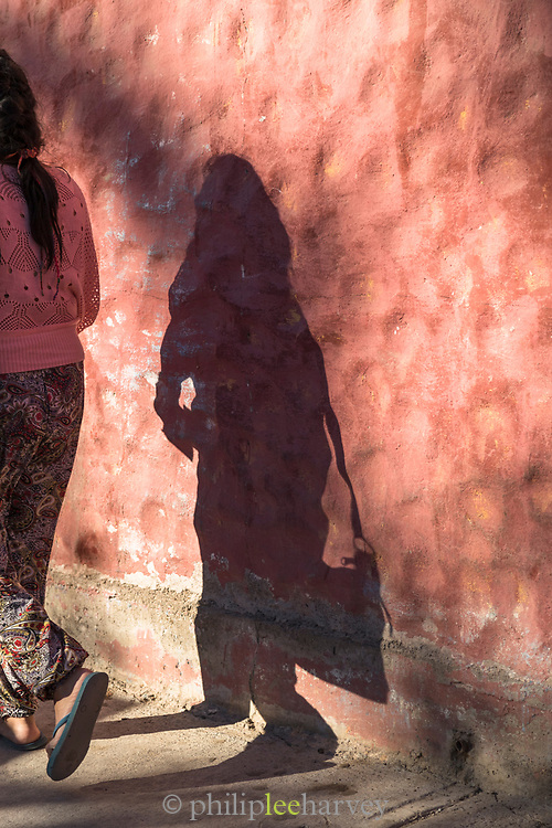Woman and her shadow on city street, Pisco Elqui, Chile