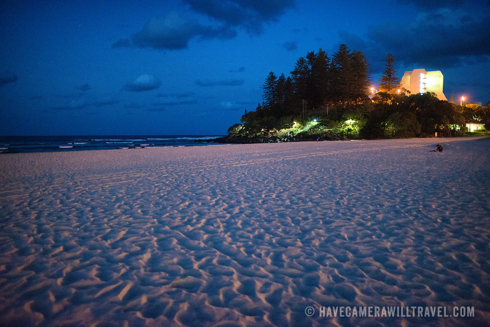 """Looking towards Pat Fagan Park over teh sand on the headland at Coolangatta at dusk. Sometimes paired as """"Twin Towns,"""" Coolangatta and Tweed Heads, on the southern end of the Gold Coast, straddle the Queensland-New South Wales border."""