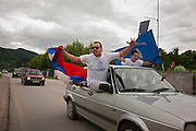 A group of young Serbian men from Srebrenica race down the central road past the Potocari Memorial Center with Serbian flags and tshirts of Ratko Mladic on Sunday May 29th, during an afternoon of many protests against Mladic's capture around the region...Matt Lutton for The International Herald Tribune..Capture of Ratko Mladic. Srebrenica, Bosnia and Herzegovina. May 29, 2011.