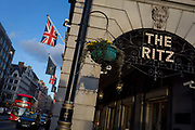 The entrance of the arcade outside The Ritz with Union Jack flags, a Routemaster bus and distant architecture on Piccadilly, on 7th February 2018, in London, England.