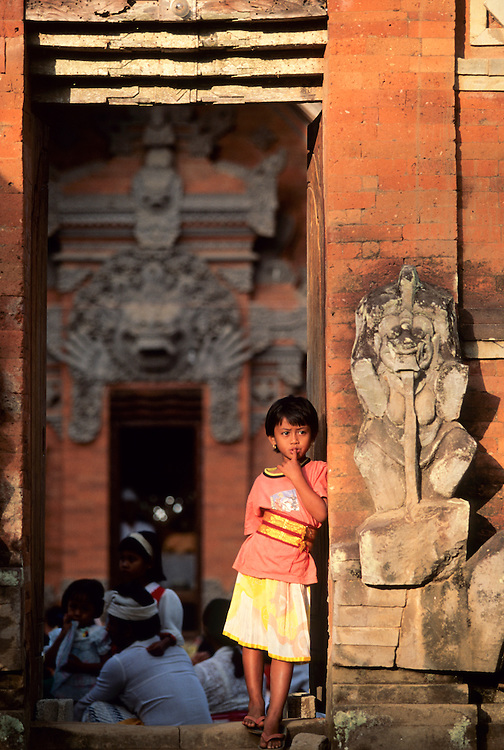 Asia, Indonesia, Bali, Ubud, girl at entrance to HIndu temple during ceremony