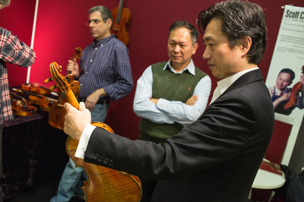 A visitor tries a violin from Scott Cao Violins, from Campbell California. Cao is in the center of the frame, in the green sleeveless sweater.