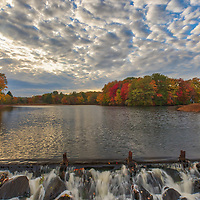 Fall foliage peak colors at Mill Pond in Ashland, Massachusetts, the overflowing water with surrounding trees covered in beautiful New England colors.<br />
