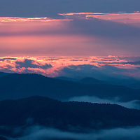 A glowing pink sunrise looking from the Looking Glass Overlook on the Blue Ridge Parkway in the Pisgah National Forest southwest of Asheville, North Carolina.