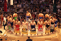 Sumo wrestlers line up in the ring before tournament commences in Tokyo