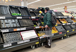 © Licensed to London News Pictures. 06/01/2021. London, UK. A shopper wearing a protective face covering picks a lemon in Sainsbury's supermarket in north London as the store runs low on fruit and vegetables, following the national lockdown. Prime Minister Boris Johnson announced on Monday 4 January 2021 that England will go into third national lockdown after the mutated variant of the SARS-Cov-2 virus continues to spread around the country, and asked everyone to 'stay at home' and only leave for the specific reasons, until mid-February. <br /> Photo credit: Dinendra Haria/LNP