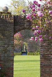 Looking through an arch from the White Garden towards the Rose Garden at Sissinghurst Castle