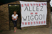 Spectators enjoy a leisurely dessert of strawberries alongside their makeshift banner to Team GB's road cycling hero Bradley Wiggins, a recent winner of the legedary Tour de France. This is the first day of competition of the London 2012 Olympic 250km mens' road race. Starting from central London and passing the capital's famous landmarks before heading out into rural England to the gruelling Box Hill in the county of Surrey. Local southwest Londoners lined the route hoping for British favourite Mark Cavendish to win Team GB first medal but were eventually disappointed when Kazakhstan's Alexandre Vinokourov eventually won gold.