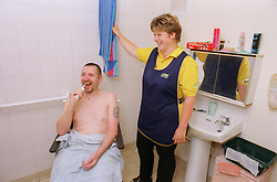 Male wheelchair user brushing teeth with carer nearby,