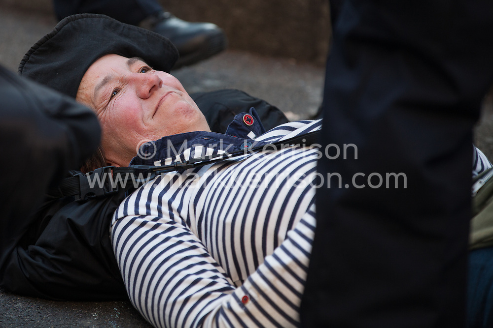 London, UK. 20th April 2019. Police officers remove climate change campaigners from Extinction Rebellion, including one pregnant woman, who had locked themselves together using an arm tube at Oxford Circus following a policing operation to clear it of protesters earlier in the day. The heart of London's shopping district was blocked until late afternoon by lock-ons on the sixth day of International Rebellion activities to call on the British government to take urgent action to combat climate change.