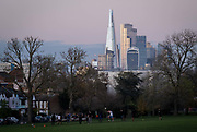 With the financial district of the City of London plus the Shard in the distance, local, football players kick a ball around in Ruskin Park, Herne Hill, on 19th November 2020, in Lambeth, London, England.