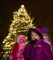 Madeline Christensen, April Miles and Taylor Miles watch Santa and Mrs. Claus light the tree at Veteran's Square following the Holiday Parade through downtown on Saturday evening.  (Karen Bobotas/for the Laconia Daily Sun)