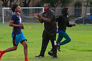 Coach Antonio McGhee gives encouragement to his squad during the North Dallas HS Bulldogs Football team's first practice since students came back to school after the onset of the Covid-19 pandemic.(Photoby Jaime R. Carrero)