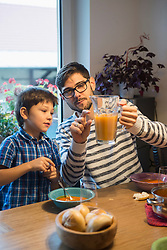 Father showing his son the measure for relation of water and juice, Munich, Germany