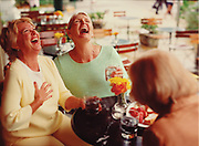 Three women laugh while spending an afternoon eating together at an outdoor cafe