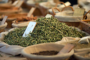 A large amount of fresh spices are available at an outdoor market in Gordes, France