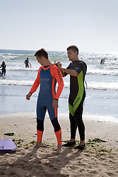 Surfers putting on wetsuits on the beach,