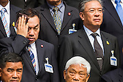 21 AUGUST 2014 - BANGKOK, THAILAND:     PANU UTHAIRAT (right), a member of the Thai National Legislative Assembly (NLA), wipes sweat from his brow during the NLA group photo session Thursday at the parliament in Bangkok. The NLA posed for group photos before meeting to select a new Prime Minster. The NLA was hand selected by the Thai junta, formally called the National Council for Peace and Order (NCPO), and is supposed to guide Thailand back to civilian rule after a military coup overthrew the elected government in May. The NLA unanimously selected General Prayuth Chan-ocha, commander of the Thai Armed Forces and leader of the coup in May that deposed the elected civilian government, as Prime Minister. Prayuth is Thailand's 29th Prime Minister since the 1932 coup that created Thailand's constitutional monarchy.    PHOTO BY JACK KURTZ