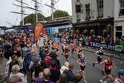 © Licensed to London News Pictures. 03/10/2021. London, UK. Spectators watch from windows as runners pass the Cutty Sark as part of the 2021 London Marathon.This London Marathon will be the first full scale staging of the race in more than two years due to the Coronavirus Pandemic.  Photo credit: George Cracknell Wright/LNP