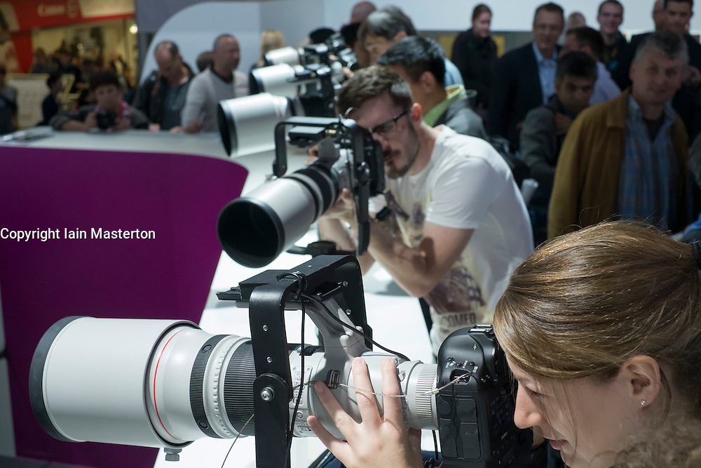 Visitors to the Canon stand try out a selection of large telephoto lenses on the second day of bi-annual Photokina photography and imaging trade fair held in Cologne Germany; Wednesday 19 September 2012