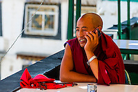 Buddhist monk talking on cellphone, Barkhor Square, Old Lhasa, Tibet (Xizang), China.
