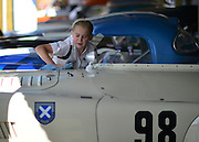 © Licensed to London News Pictures. 14/09/2012. Goodwood, UK A young girl cleans a car. People enjoy the atmosphere at the 2012 Goodwood Revival Meeting today 14 September 2012. The event recreates the glorious days of motor racing and participants are encouraged to dress in period dress. Photo credit : Stephen Simpson/LNP