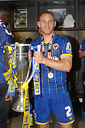 Barry Fuller (Captain) defender for AFC Wimbledon (2) holds the trophy as AFC Wimbledon win promotion to league 1after the Sky Bet League 2 play off final match between AFC Wimbledon and Plymouth Argyle at Wembley Stadium, London, England on 30 May 2016. Photo by Stuart Butcher.