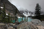 Moraine Lake, near Lake Louise - a beautiful lake surrounded by mountains, unfortunately obscured by cloud. Many trees lie at one end of the lake.