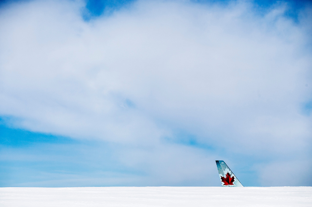 A tail of an Airbus A320 that slid off a runway at the end of Air Canada Flight 624 at Halifax Stanfield Airport sits behind snow in Enfield, Nova Scotia, March 30, 2015. An Air Canada plane that suffered heavy damage in an accident in the east coast city of Halifax on Sunday landed short of the runway and hit an antenna array, losing its landing gear, safety officials said. No one was killed in the accident that sent more than 20 passengers and crew to hospital. All but one of those treated had been released by later in the day, the airline said. REUTERS/Mark Blinch