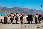 Group of Kazakh eagle hunters riding through the village together with their eagles wearing their bright red fur hats,  Altai Mountains, Bayan Ulgii, Mongolia