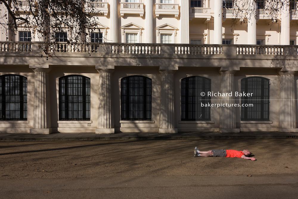 An exhausted jogger has collapsed and lies on his back on the gravel outside the ICA in London's The Mall.
