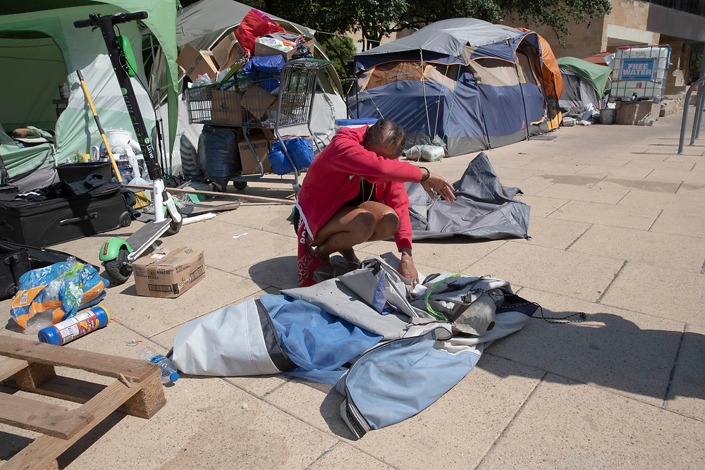 Naquila Chambers-Moore waits as City of Austin  (TX) police supervise while city workers clean out a large homeless protest camp on the north side of City Hall mid-morning. Police arrested multiple homeless who refused to cooperate after several weeks of warnings and offers of assistance