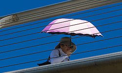 London, July 18th 2016. A woman with a pink umbrella crosses the Millennium Bridge as London's temperatures soar to 29º C.