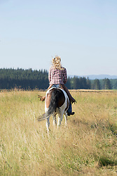 Rear view of a mid adult woman riding a horse in farm, Bavaria, Germany