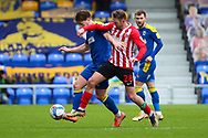 AFC Wimbledon midfielder Alex Woodyard (4) battles for possession with Sunderland attacker Aiden McGeady (28) during the EFL Sky Bet League 1 match between AFC Wimbledon and Sunderland at Plough Lane, London, United Kingdom on 16 January 2021.