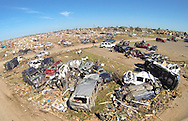A pile of destroyed cars of teachers sits outside Briarwood elementary school in Oklahoma City, Oklahoma May 22, 2013.  Rescue workers with sniffer dogs picked through the ruins on Wednesday to ensure no survivors remained buried after a deadly tornado left thousands homeless and trying to salvage what was left of their belongings. Curvature of horizon in the photo is due to an ultra-wide angle lens.  REUTERS/Rick Wilking (UNITED STATES)
