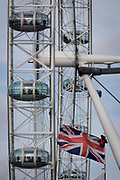 Tourist passengers enjoy the ride in the pods of the  London eye tourist attraction on the Southbank. The Union Jack flag flies in a stiff breeze at the bottom of the picture with the Eye in the background. The London Eye's  rotation takes about 30 minutes, meaning the capsules that hold a family or group of fare-paying passengers in pods travel at a stately 26cm per second, or 0.9km (0.6 miles) per hour. Since opening in 2000, an average of 3.75 million visitors have experienced London's most-visited attraction each year while the modernist Festival Hall, which was built as part of the post-war Festival of Britain of 1951 though altered in 1964.