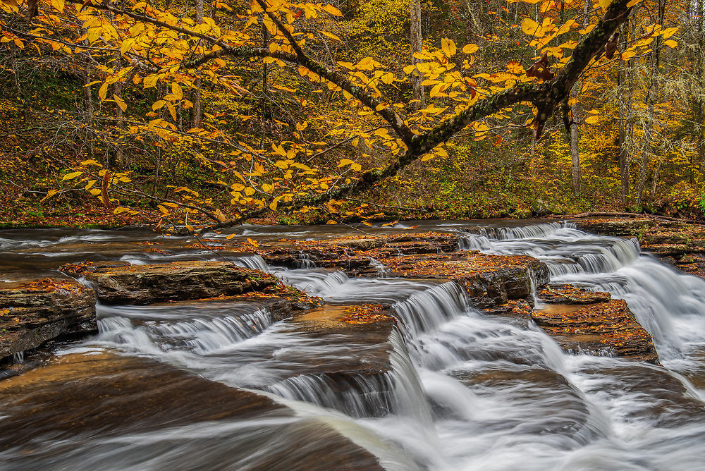 Bright autumn oranges decorate the stair-step falls at Camp Creek State Park in West Virginia.