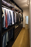 Walk-in closet full of clothes. Mirror resting on the ground and spotlights to illuminate the scene