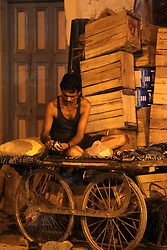 A snack before bed.  A man peels some fruit before sleeping on his cart in New Delhii India.  The Commonwealth Games are being held in Delhi India between the 3rd and 14th October 2010..Photoby:  Ron Gaunt/SPORTZPICS