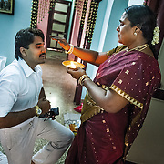 Before heading out to attend the prayer ceremony at the wedding venue , the groom's mother performes a small blessing for her son. Madurai, Tamil Nadu, 2009