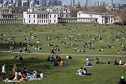 © Licensed to London News Pictures. 04/04/2021. London, UK. Members of the public relax and enjoy the sunny weather in Greenwich Park in South East London. Temperatures are expected to rise with highs of 16 degrees forecasted for parts of London and South East England today . Photo credit: George Cracknell Wright/LNP