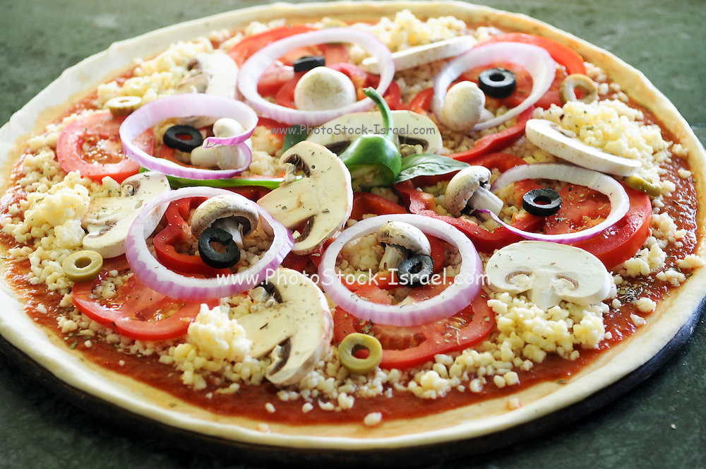 Onion, mushroom, and olive pizza before baking