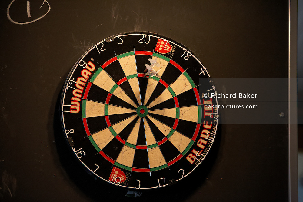 A dart board with three arrows scoring well and embedded in the circular