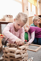 Little girl playing with wooden building bricks in her kindergarten