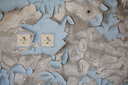 Light switches in a bedroom of Hotel Polissia. The peeling paint is the result of 21 years decay.