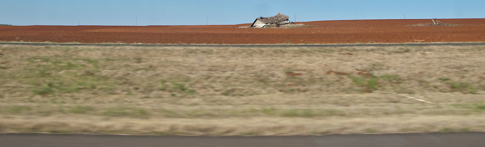 a collapsed farmhouse in a plowed field in flat rural west Texas along interstate 20